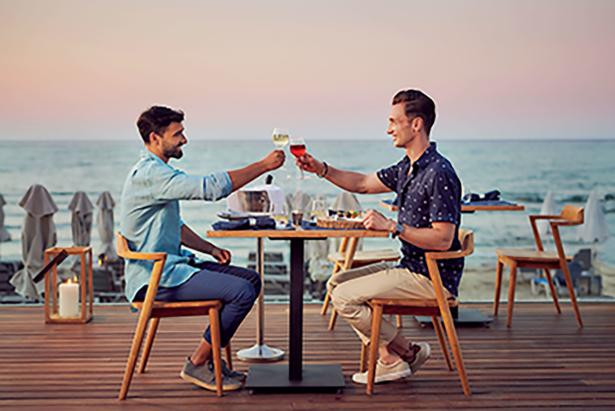 Männer sitzen am Meer mit einem Glas Sekt